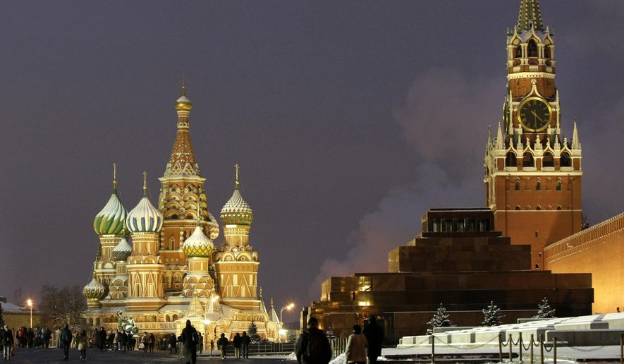 In this Dec. 10, 2009, file photo, people walk in Red Square, with St. Basil Cathedral, left, the Kremlin's Spassky Tower, right back, and Lenin Mausoleum, right, in Moscow, Russia. (AP Photo/Misha Japaridze, File) **FILE**