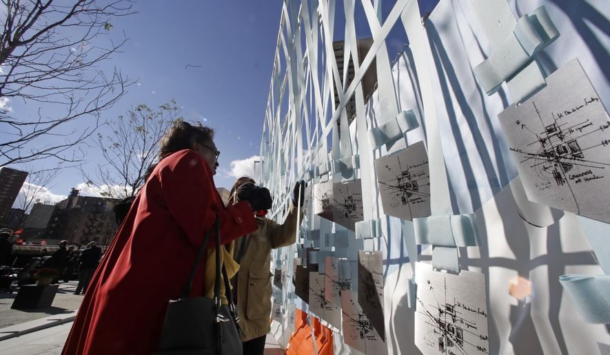 Patrons take keepsakes during a ceremony to dedicate the new Manhattanville campus of Columbia University on Monday, Oct. 24, 2016, in New York. The university said it will officially open its new West Harlem campus next spring as part of a $6.3 billion project that will unfold over several decades. (AP Photo/Frank Franklin II)