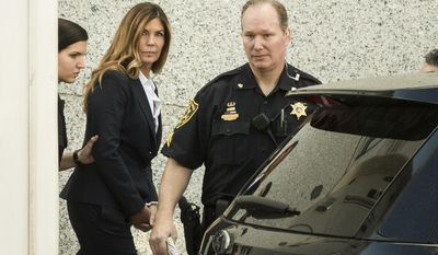 CORRECTS TO AFTER SENTENCING HEARING, NOT BEFORE - Former Pennsylvania Attorney General Kathleen Kane is escorted from Montgomery County courthouse after her sentencing hearing in Norristown, Pa, Monday, Oct. 24, 2016. Kane was sentenced Monday to 10 to 23 months in jail for illegally disclosing details from a grand jury investigation to embarrass a rival and lying about it under oath. (AP Photo/Matt Rourke)