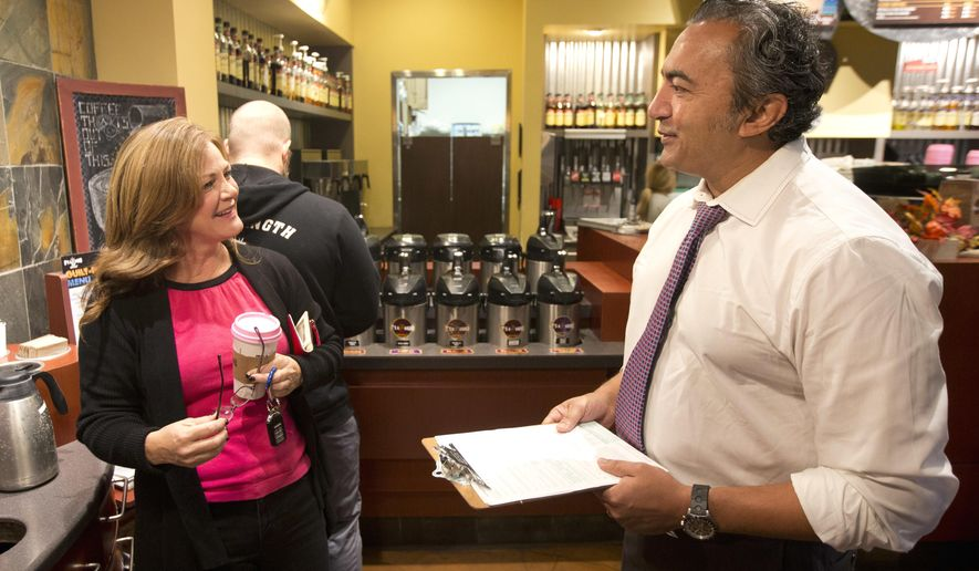 Rep. Ami Bera, D-Elk Grove, talks with Laura Smith about voting, in Elk Grove, Calif., Monday, Oct. 24, 2016. Bera was out urging people to register and vote as Monday is the last day for Californians to register for the November election. Smith said she is registered and votes by mail. Bera is in a tight race against challenger, Republican Scott Jones, the sheriff of Sacramento County for California's 7th Congressional seat. (AP Photo/Rich Pedroncelli)