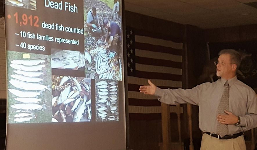In this Oct. 13, 2016 photo, Christopher Urban of the Pennsylvania Fish & Boat Commission points to a slideshow of the 2009 fish kill in Dunkard Creek along the Pennsylvania-West Virginia line while discussing where the recovery effort stands during a meeting with the public at the Mt. Morris Sportsman Club in Pennsylvania. It has been more than seven years since an algae bloom wiped out aquatic life in portions of Dunkard Creek, but the full recovery is still years away. (Mike Jones/Observer-Reporter via AP)