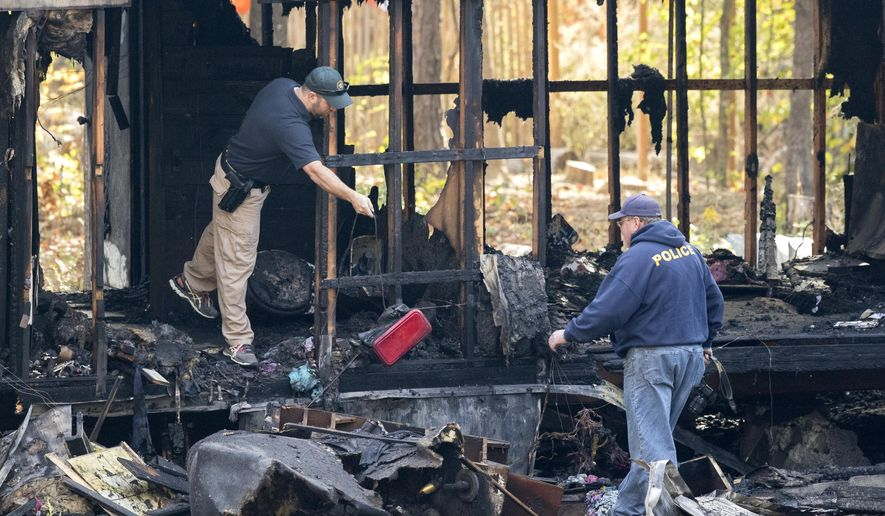 Investigators work the scene at 1120 Airport Road near Trion, Ga., where multiple people were killed in an overnight fire that engulfed a single wide trailer home in Trion, Ga. State officials say the fire was caused by an improperly installed wood stove. (Dan Henry/The Chattanooga Times Free Press via AP)
