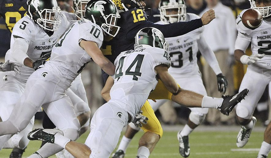 FILE - In this Oct. 17, 2015, file photo, Michigan punter Blake O'Neill (12) fumbles the ball as he is surrounded by Michigan State defenders in the closing seconds of the second half of an NCAA college football in Ann Arbor, Mich. Michigan State's Jalen Watts-Jackson grabbed the ball and ran it in for a touchdown and a 27-23 win. (Dale G. Young/Detroit News via AP, File)