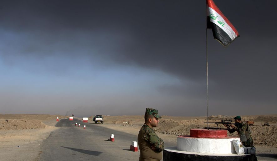 FILE -- In this Saturday, Oct. 22, 2016 file photo, Iraqi troops guard a checkpoint near the village of Awsaja, Iraq, as smoke from fires lit by Islamic State militants at oil wells and a sulfur plant fills the air. In the week since Iraq launched an operation to retake Mosul from the Islamic State group, its forces have pushed toward the city from the north, east and south, battling the militants in a belt of mostly uninhabited towns and villages. In the heavily mined approaches to the city they met with fierce resistance, as IS unleashed suicide truck bombs, rockets and mortars. (AP Photo/Adam Schreck, File)