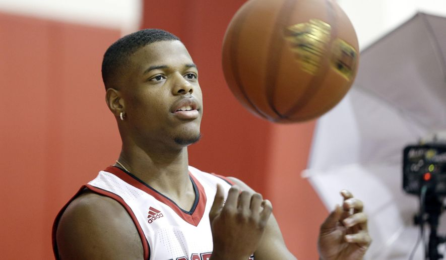 FILE - In this Sept. 29, 2016, file photo, North Carolina State's Dennis Smith Jr. tosses a ball while being photographed during the NCAA college basketball team's media day in Raleigh, N.C. Smith enrolled early in January to focus on recovering from a serious knee injury suffered before his senior year of high school. (AP Photo/Gerry Broome, File)