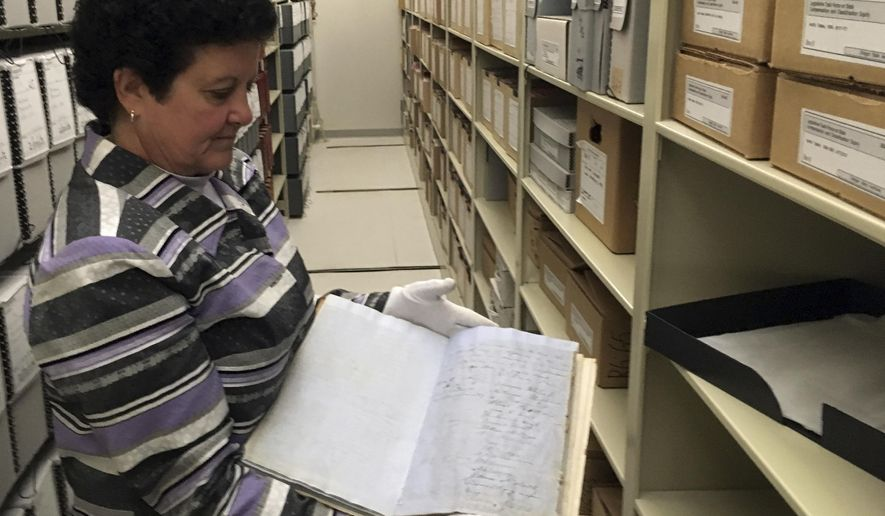In this Oct. 10, 2016 photo, Oregon State Archivist Mary Beth Herkert holds Oregon's original constitution in Salem, Ore. Signed in 1857, it is becoming tattered and torn. Herkert is trying to raise money to restore it, buy a case to display it and preserve it. The constitution contains a clause prohibiting blacks from residing in the state, which Herkert calls shameful but says shouldn't be hidden. (AP Photo/Andrew Selsky)