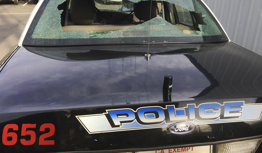 This Oct. 23, 2016, photo provided by the Madera Police Department shows a patrol car that was shot at in Madera, Calif. Central California police are looking for the gunman who fired more than a dozen rounds at an officer and a civilian who was on a ride-along. The incident occurred early Sunday morning as the Madera officer tried to stop the vehicle and a pursuit ensued. (Madera Police Department via AP)