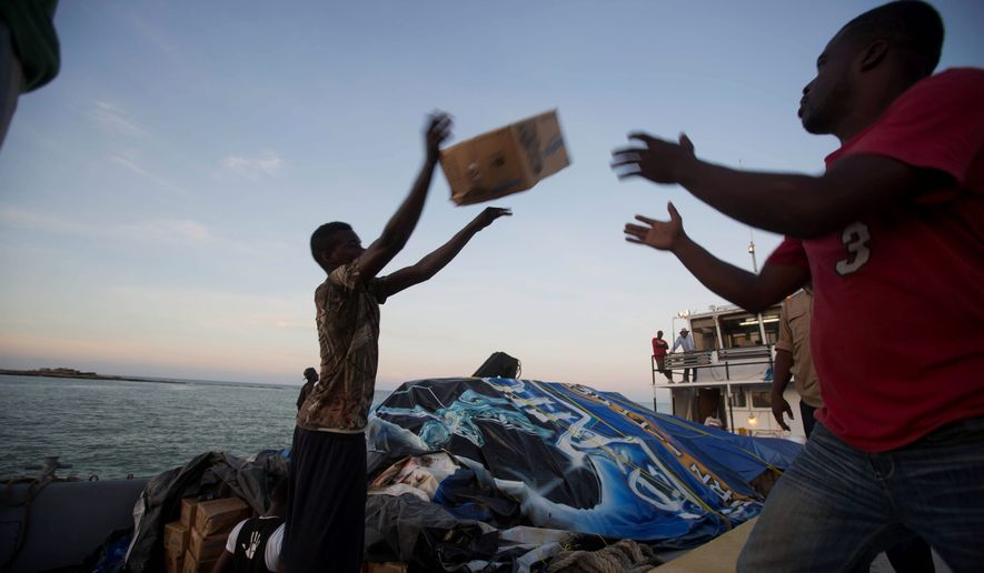 "People unload food and water boated in from the ""Mission of Hope"" charity after Hurricane Matthew swept through Jeremie, Haiti, on Oct. 8. (Associated Press)"