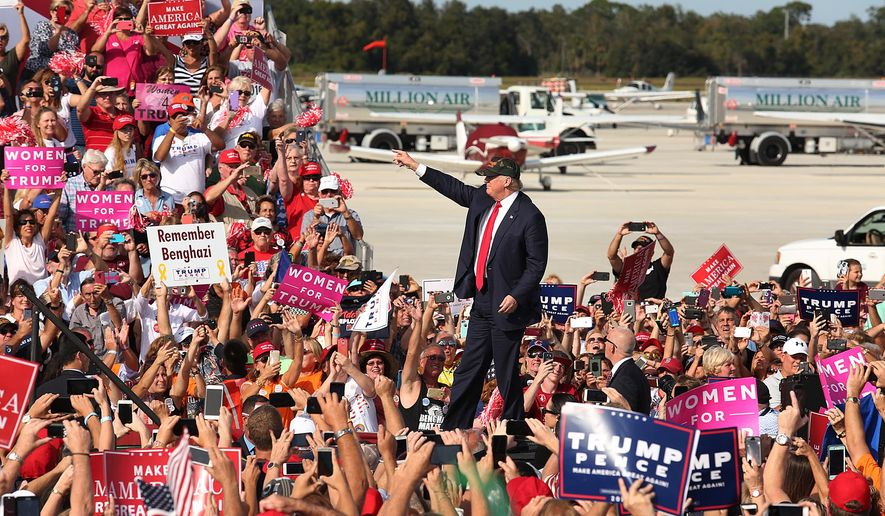 Donald Trump waves to cheering supporters at a Trump rally at Sanford Orlando International Airport in Sanford, Fla., Tuesday, Oct. 25, 2016. Trump is pledging to bolster the government's investment in the space program, a boon to the Space Coast of Florida. (Stephen M. Dowell/Orlando Sentinel via AP)
