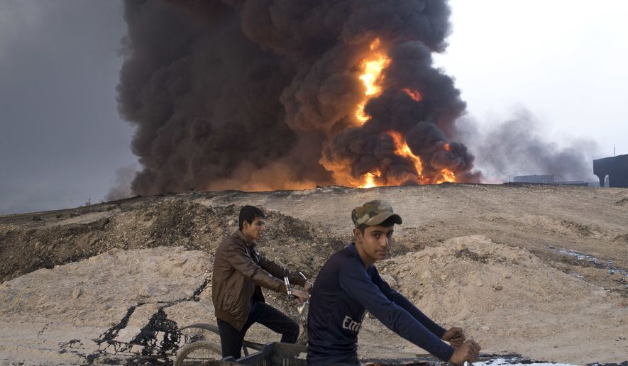 FILE - In this Sunday, Oct. 23, 2016 file photo, youths ride bicycles next to a burning oil well in Qayara, about 31 miles (50 km) south of Mosul, Iraq. The Islamic State group has pioneered brutally innovative tactics and launched diversionary attacks that have shocked its opponents, and now many fear it has more surprises in store as Iraqi forces close in on Mosul. Last weeks assault on the northern city of Kirkuk offers a glimpse at the kind of asymmetrical response it might mount as Iraqi forces close in on Mosul, its last major urban bastion in the country. (AP Photo/Marko Drobnjakovic, File)