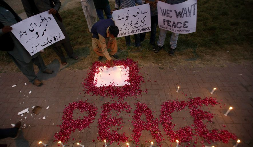 A Christian adjusts a candle next to wording 'Peace' drawn with rose petals during a candlelight vigil for the victims of an overnight attack on the Quetta Police Training Academy, in Islamabad, Pakistan, Tuesday, Oct. 25, 2016. Militants wearing suicide vests stormed a Pakistani police academy in the southwestern city of Quetta overnight, killing dozens of people, mostly police cadets and recruits, and waging a ferocious gun battle with troops that lasted into early hours Tuesday. (AP Photo/Anjum Naveed)