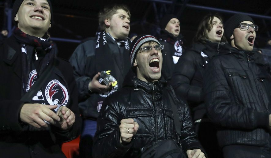 """CORRECTING IDENTIFICATION TO SOCCER FANS - FILE - In this photo taken on Friday, Oct. 21, 2016, Krumkachy soccer fans react during a match between Krumkachy and Granit in Minsk, Belarus.  Krumkachy, """"Ravens""""  soccer club has rocketed into the Belarusian Top League with back-to-back promotions and a shoestring budget, plus an enthusiastic fan base combining hipsters, families and others turned off by the stagnation of football in the ex-Soviet nation. (AP Photo/Sergei Grits, FILE)"""