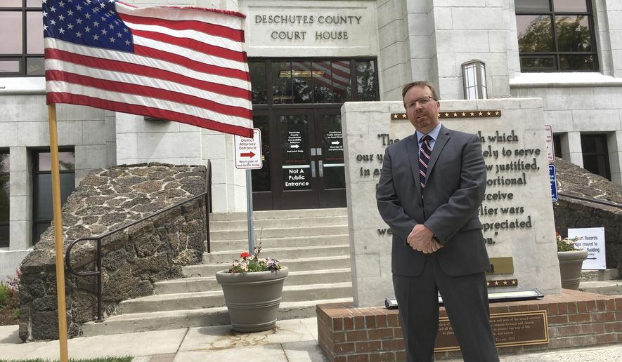 FILE - In this May 15, 2016, file photo, Deschutes County District Attorney John Hummel stands in front of the county courthouse in Bend, Ore. Hummel is objecting to a judge's gag order on a murder case, saying it violates freedom of speech and infringes on both his ability to consult with the victim's family members on potential plea bargaining and on his rights to communicate with the citizens he was elected to represent. (AP Photo/Andrew Selsky, File)