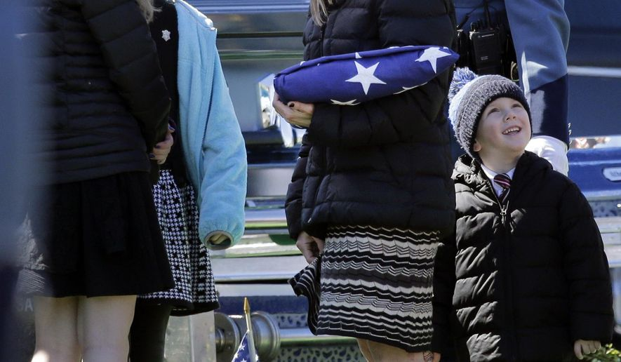 FILE - In this March 22, 2016 file photo, Reisa Clardy, the widow of Mass. State Trooper Thomas L. Clardy, holds a folded flag as she and her children watch balloons fly during his funeral in Hudson, Mass. As Massachusetts voters prepare to decide whether to legalize recreational marijuana use, the widow of a state trooper and father of seven killed when a driver high on marijuana barreled into his cruiser, is making an emotional plea against a ballot question that would legalize recreational marijuana. (AP Photo/Elise Amendola, File)