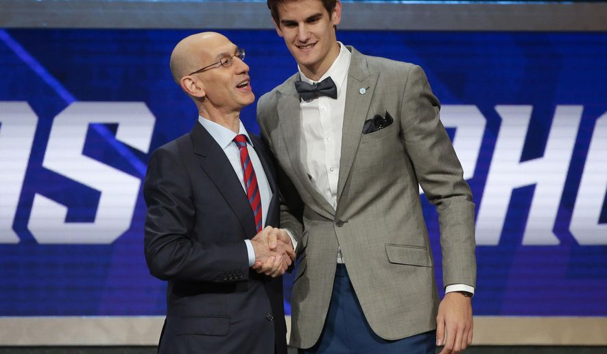 FILE - In this June 23, 2016, file photo, NBA Commissioner Adam Silver, left, congratulates Dragan Bender, of Croatia, after Bender was selected fourth overall by the Phoenix Suns during the NBA basketball draft,  in New York. The NBA begins its season Tuesday night, Oct. 25, 2016, with international players making up one-quarter of the league. (AP Photo/Frank Franklin II, File)