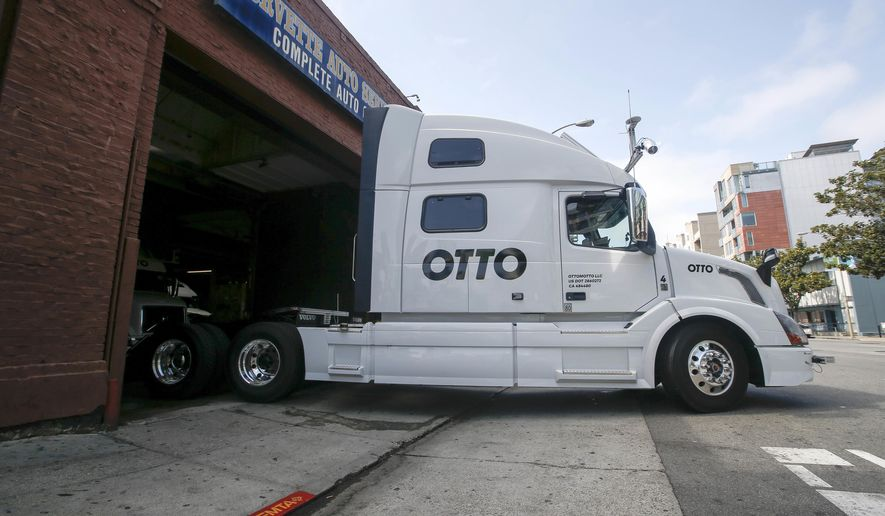 FILE - In this Aug. 18, 2016, file photo, one of Otto's self-driving, big-rig trucks leaves the garage for a test drive during a demonstration at the Otto headquarters in San Francisco. Anheuser-Busch announced on Oct. 25, 2016, that it teamed up with Otto for a 120-plus mile beer delivery that marked the world's first by a self-driving truck. (AP Photo/Tony Avelar, File)