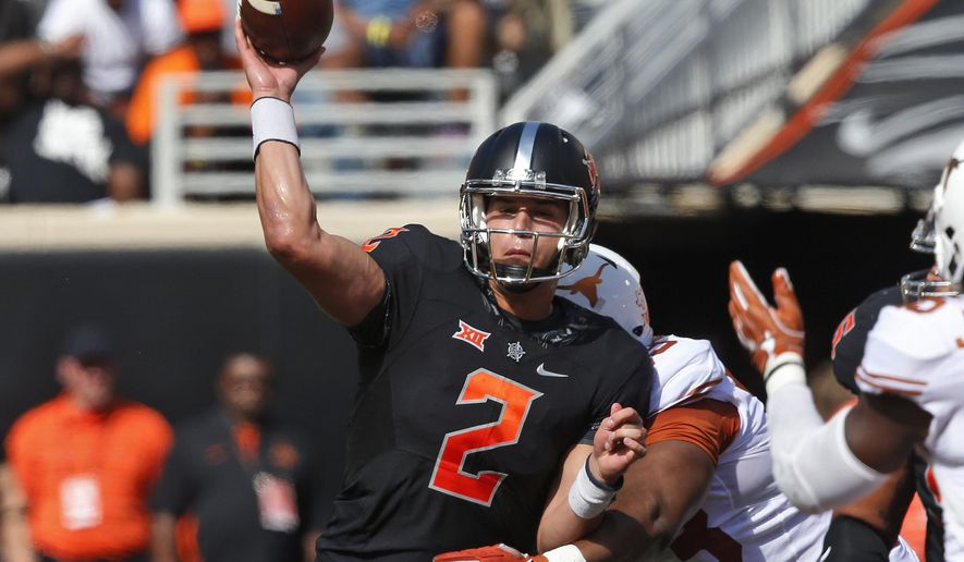 FILE - In this Oct. 1, 2016, file photo, Oklahoma State quarterback Mason Rudolph (2) throws as he is hit by Texas defensive tackle Paul Boyette Jr. (93) in the first quarter of an NCAA college football game in Stillwater, Okla. Rudolph is the third straight quarterback that No. 10 West Virginia will face who is averaging at least 320 passing yards per game. (AP Photo/Sue Ogrocki, File)