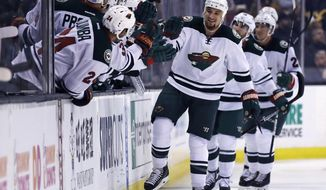 Minnesota Wild right wing Chris Stewart, center, is congratulated by teammates after his goal against Boston Bruins goalie Malcolm Subban during the second period of an NHL hockey game in Boston, Tuesday, Oct. 25, 2016. (AP Photo/Charles Krupa)
