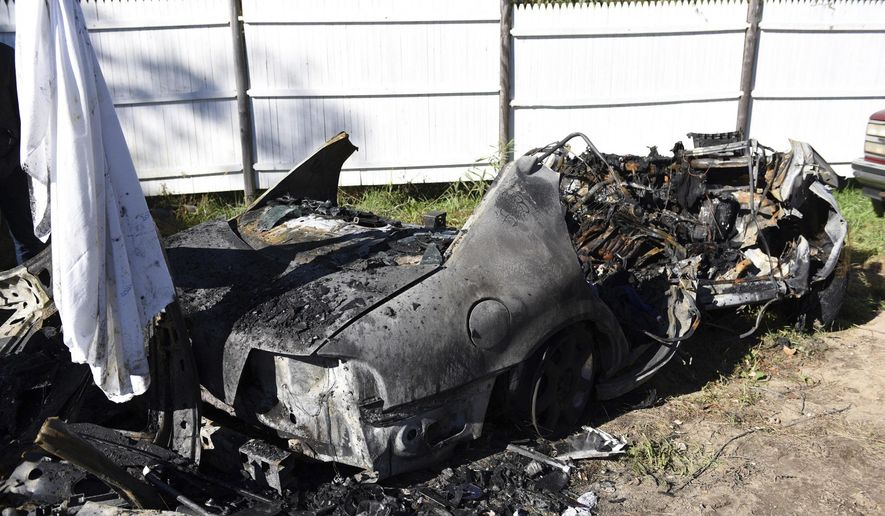 The remains of a car that carried four college students and was involved in a fiery crash as a result of being struck head-on while driving on the northbound side of Interstate 495 sit at Marc's Towing company, Monday, Oct. 24, 2016, in Wareham, Mass. Five people, including the four college students, died early Monday in a fiery crash caused by a woman driving the wrong way on a Massachusetts highway, state police said. (Faith Ninivaggi/The Boston Herald via AP)