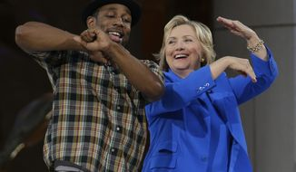 """Democratic presidential candidate Hillary Rodham Clinton, right, practices her dance moves with DJ Stephen """"tWitch"""" Boss during a break in the taping of The Ellen DeGeneres Show, Tuesday, Sept. 8, 2015, at Rockefeller Center in New York. (AP Photo/Mary Altaffer)"""