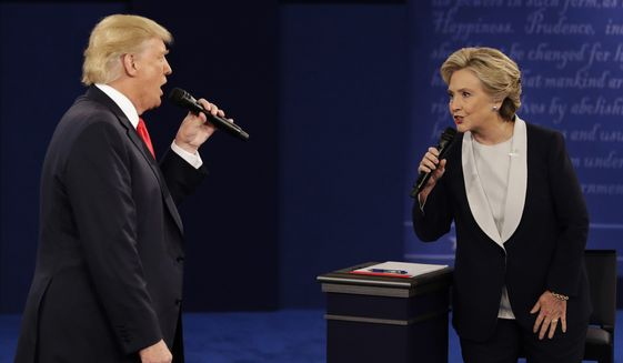 Republican presidential nominee Donald Trump and Democratic presidential nominee Hillary Clinton speak during the second presidential debate at Washington University in St. Louis. (AP Photo/John Locher, File) **FILE**