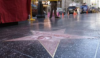 A man stands near a cordoned off area surrounding the vandalized star for Republican presidential candidate Donald Trump on the Hollywood Walk of Fame, Wednesday, Oct. 26, 2016, in Los Angeles. Det. Meghan Aguilar said investigators were called to the scene before dawn Wednesday following reports that Trump's star was destroyed by blows from a hammer. (AP Photo/Richard Vogel)