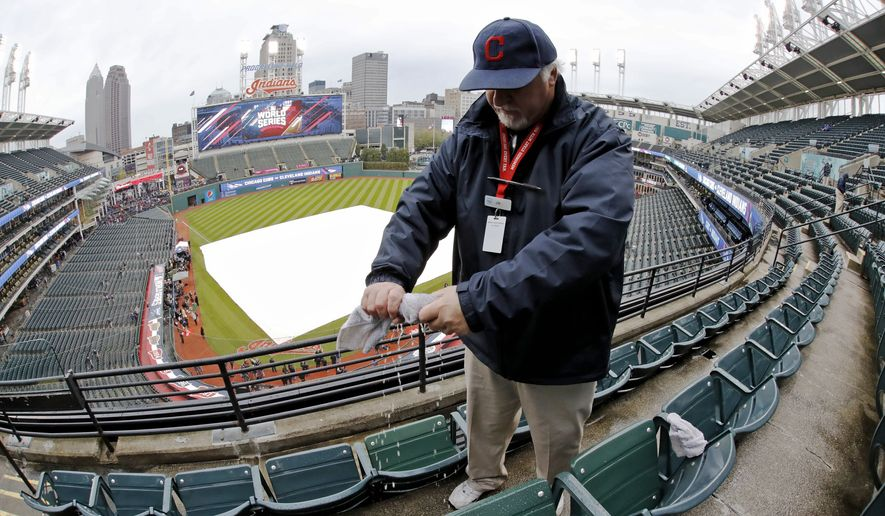 An usher wipes water from some seats at Progressive Field before Game 2 of the Major League Baseball World Series between the Cleveland Indians and the Chicago Cubs Wednesday, Oct. 26, 2016, in Cleveland. (AP Photo/Gene J. Puskar)