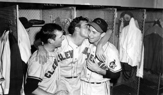 FILE - In this Oct. 11, 1948, file photo, Cleveland Indians relief pitcher Gene Bearden, center, embraces his teammates,  starting pitcher Bob Lemon, left, and catcher Jim Hegan as they celebrate in the dressing room after winning the World Series in Boston, Mass., with a 4-3 win against the Boston Braves to take the series four games to two. (AP Photo/File)