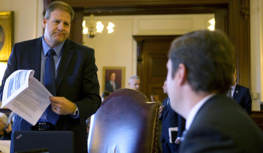 Democratic candidate for governor, Executive Councilor Colin VanOstern, right listens to his Republican rival for governor, Executive Councilor Chris Sununu during the last Executive Council meeting before the election Wednesday, Oct. 26, 2016, in Concord, N.H. Sununu and Van Ostern will face each other Wednesday night for a debate being broadcast by NH-1 news. (AP Photo/Jim Cole)