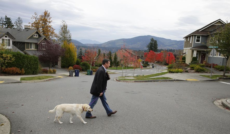 In this photo taken Oct. 24, 2016, Sen. Mark Mullet, D-Issaquah, walks with his dog Arthur as he rings doorbells of registered voters in Issaquah, Wash. Mullet is being challenged for his seat in the state legislature by State Rep. Chad Magendanz, R-Issaquah. (AP Photo/Ted S. Warren)