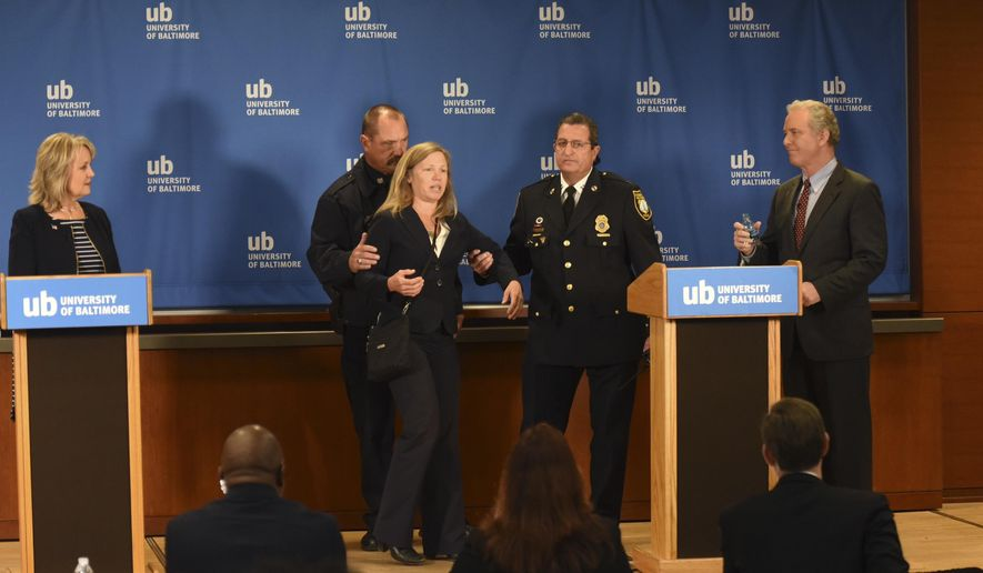 Margaret Flowers, center, the Green Party candidate for U.S. Senate in Maryland, is escorted off stage after interrupting a televised Senate debate between Rep. Kathy Szeliga, R-Baltimore County, left, and Rep. Chris Van Hollen, D-Md., in Baltimore, Wednesday, Oct. 26, 2016. Flowers was not invited to participate in the debate. The candidates are running for the seat that's opening up with the retirement of Barbara Mikulski, who is leaving office after 30 years. (Amy Davis/The Baltimore Sun via AP)