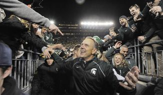 FILE - In this Oct, 17, 2015, file photo, Michigan State head coach Mark Dantonio smiles as he greets fans while leaving the field after the Spartans' 27-23 win over Michigan in an NCAA college football game in Ann Arbor, Mich.  Dantonio believes Michigan State will upset No. 2 Michigan and he's not afraid to say it. In fact, Dantonio said in an interview with The Associated Press the Spartans' chances of winning Saturday are better than they were with 10 seconds left in last year's game at Michigan Stadium. (John Greilick/Detroit News via AP, File)