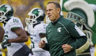 FILE - In this Oct. 17, 2015, file photo, Michigan State head coach Mark Dantonio, runs on to the Michigan Stadium field with his team before an NCAA college football game against Michigan in Ann Arbor, Mich. Dantonio believes Michigan State will upset No. 2 Michigan and he's not afraid to say it. In fact, Dantonio said in an interview with The Associated Press the Spartans' chances of winning Saturday are better than they were with 10 seconds left in last year's game at Michigan Stadium. (AP Photo/Tony Ding, File0