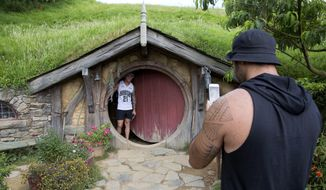 """In this Thursday, Dec. 31, 2015 photo, tourists take photos during a tour of the Hobbit movie set near Matamata, New Zealand. In New Zealand there are twice as many cows as people, but it's the hobbits that are really making hay. According to figures released Wednesday, Oct. 26, 2016, tourism has overtaken dairy as the nation's top earner of overseas dollars. And tourism officials say the success of the fantasy movie trilogy """"The Hobbit"""" has helped.(AP Photo/Mark Baker)"""
