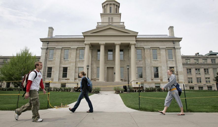 In this May 3, 2006, file photo, University of Iowa students walk past the Old Capitol building in Iowa City, Iowa a few days before the building was to open to the public for the first time since being heavily damaged in a fire on Nov. 20, 2001. (AP Photo/Charlie Neibergall, File)  **FILE**