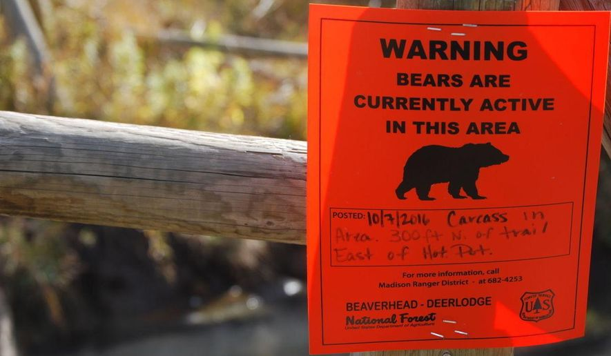 ADVANCE FOR THE WEEKEND OF OCT. 29-30 AND THEREAFTER - A sign on the fence surrounding Upper Potosi hot springs near Pony, Mont., Oct. 19, 2016, warns of increased bear activity in the area, thanks to a moose carcass that was found nearby earlier in the month. (Whitney Bermes/Bozeman Daily Chronicle via AP)