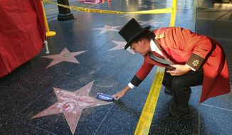 Gregg Donovan, who calls himself the unofficial ambassador of Hollywood, places a sticker for Republican presidential candidate Donald Trump on Trump's vandalized star on the Hollywood Walk of Fame, Wednesday, Oct. 26, 2016 in Los Angeles. Det. Meghan Aguilar said investigators were called to the scene before dawn Wednesday following reports that Trump's star was destroyed by blows from a hammer. (AP Photo/Richard Vogel)
