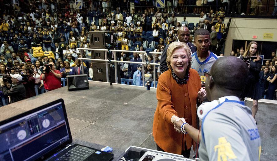 Democratic presidential candidate Hillary Clinton greets a DJ on stage after speaking at a homecoming pep rally at North Carolina Agricultural and Technical State University in Greensboro, N.C., Thursday, Oct. 27, 2016. (AP Photo/Andrew Harnik)