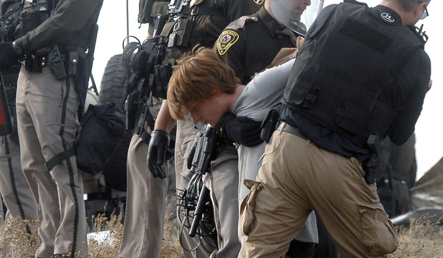 An unidentified Dakota Access Pipeline protester is arrested inside the Front Line Camp as law enforcement surround the camp to remove the protesters from the property and relocated to the overflow camp a few miles south of Highway 1806 in Morton County, N.D., Thursday, Oct. 27, 2016. (Mike McCleary/The Bismarck Tribune via AP) **FILE**