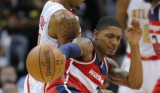 Washington Wizards guard Bradley Beal (3) briefly loses control of the ball as Atlanta Hawks forward Kent Bazemore (24) defends in the first half on an NBA basketball game Thursday, Oct. 27, 2016, in Atlanta. (AP Photo/John Bazemore)