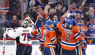 Washington Capitals' goalie Braden Holtby (70) looks on as the Edmonton Oilers celebrate a goal during the third period of an NHL hockey game in Edmonton, Alberta, Wednesday, Oct. 26, 2016. (Jason Franson/The Canadian Press via AP)