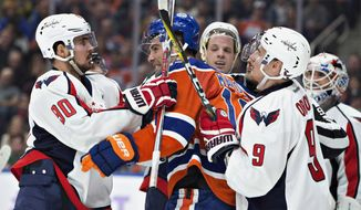 Washington Capitals' Marcus Johansson (90) and Edmonton Oilers' Patrick Maroon (19) rough it up as Dmitry Orlov (9) tries to hold back Patrick Maroon (19) during the second period of an NHL hockey game in Edmonton, Alberta, Wednesday, Oct. 26, 2016. (Jason Franson/The Canadian Press via AP)