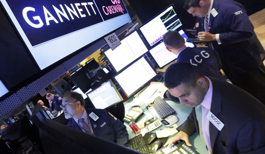 FILE - In this Aug. 5, 2014, file photo, specialist Michael Cacace, foreground right, works at the post that handles Gannett on the floor of the New York Stock Exchange. USA Today publisher Gannett, suffering from the ongoing print-ad declines that have hurt the broader newspaper industry, is cutting jobs as it reported a loss in its latest quarter, the company announced Thursday, Oct. 27, 2016. (AP Photo/Richard Drew, File)