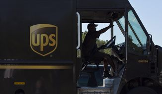 In this Sept. 23, 2014, file photo, a United Parcel Service truck driver enters a company warehouse in Birmingham, Ala. UPS reports financial results Thursday, Oct. 27, 2016. (AP Photo/Brynn Anderson, File)