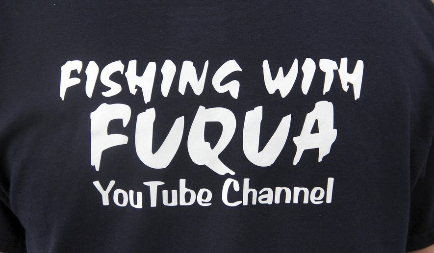 ADVANCE FOR USE SUNDAY, OCT. 30, 2016 AND THEREAFTER - In this Oct. 3, 2016 photo, Dylan Fuqua wears a T-shirt promoting his YouTube channel  while fishing near at Crab Orchard Lake outside of Carterville, Ill. Fuqua, is so captivated by the sport he has his own YouTube channel, Fishing With Fuqua. And, he recently purchased a bait shop, not bad for a seventh grader. While it's tempting to write off Fuqua as an idealistic 12-year-old, he earned some credibility during the Southern Illinois Celebration of National Hunting and Fishing Days, winning the King Catfish Tournament.(Les Winkeler/The Southern, via AP) )