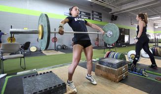 ADVANCE FOR USE SUNDAY, OCT. 30, 2016 AND THEREAFTER - In this Sept.  19, 2016 photo 13-year-old weight lifter Abby Raymond trains at CrossFit Rise in Schaumburg, Ill. She will compete at the Mid-American Weightlifting Championship later this month in Schaumburg. Her coach Roger Nielsen thinks Abby has a good chance to reach the pinnacle of the sport. (Steve Lundy/Daily Herald, via AP)