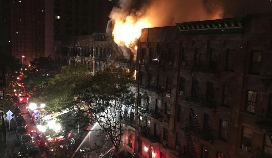 Firefighters work to put out a blaze at an apartment building on the Upper East Side in New York on Thursday, Oct. 27, 2016. The flames quickly spread throughout the building and were shooting out the roof at one point, sending burning embers onto nearby buildings. (Matt Bonaccorso via AP)