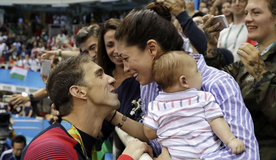 In this Aug. 9, 2016, file photo, United States' swimmer Michael Phelps celebrates winning his gold medal in the men's 200-meter butterfly with his fiance Nicole Johnson and baby Boomer during the swimming competitions at the 2016 Summer Olympics, in Rio de Janeiro, Brazil. The Arizona Republic reported Oct. 26, 2016, that Phelps and Johnson secretly married on June 13, 2016. (AP Photo/Matt Slocum, File)