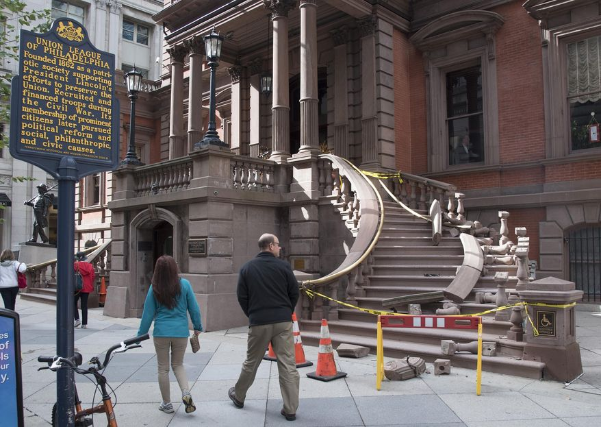 Pedestrians look at the north side of the grand staircase entrance to The Union League in Philadelphia, which was damaged in the early morning hours of Monday, Oct. 24, 2016 as someone apparently tried to rip the brass railing off its supports to resell for money.   (Clem Murray/The Philadelphia Inquirer via AP)