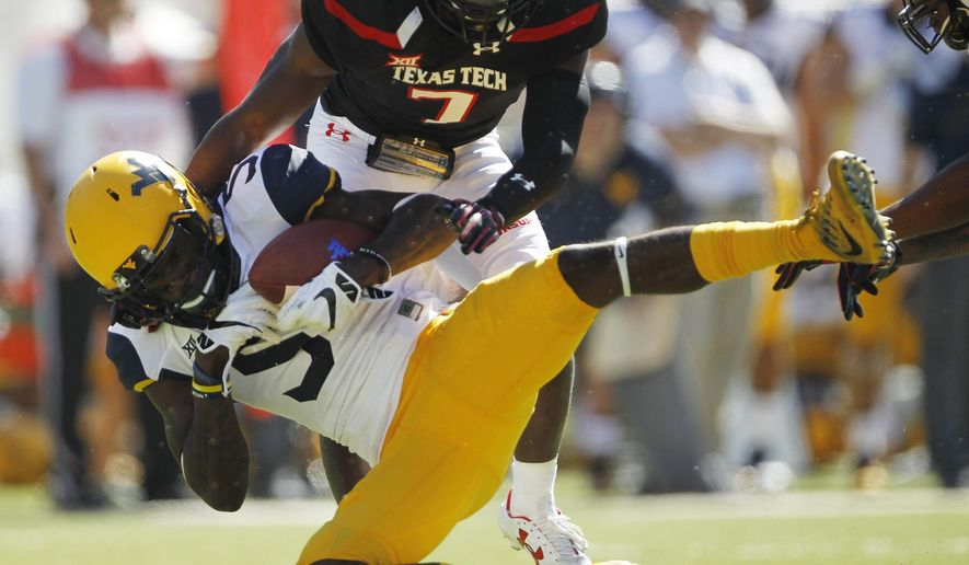 FILE - In this Saturday, Oct. 15, 2016, file photo, West Virginia wide receiver Jovon Durante is tackled by Texas Tech defensive back Jah'shawn Johnson in the second quarter of an NCAA college football game at Jones AT&T Stadium in Lubbock, Texas. Durante was among a group of receivers that made diving catches last week against TCU and will be looking for more on Saturday when No. 10 West Virginia travels to play Oklahoma State.(Mark Rogers/Lubbock Avalanche-Journal via AP, File) /Lubbock Avalanche-Journal via AP)